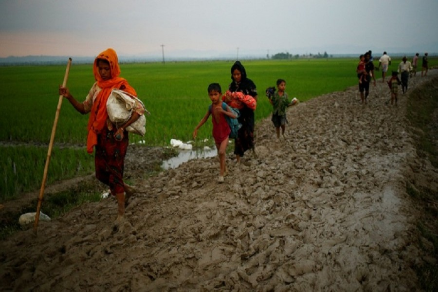 A Rohingya refugee walks on the muddy path after crossing the Bangladesh-Myanmar border in Teknaf. Reuters