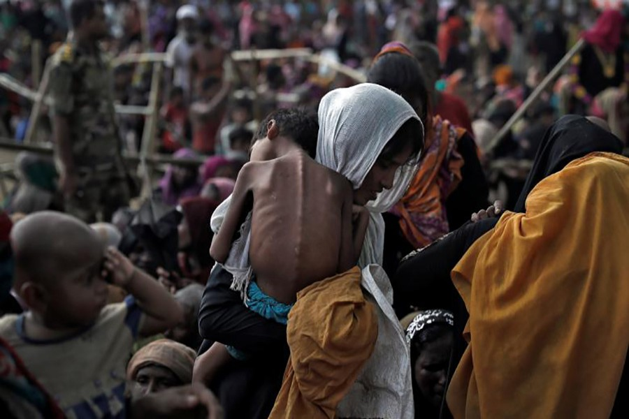 A woman carries her ill child in a refugee camp at Cox's Bazar, Bangladesh.  Approximately 480,000 Rohingya Muslims have fled to Bangladesh since August following an Army crackdown in Myanmar's Rakhine State.- Reuters photo