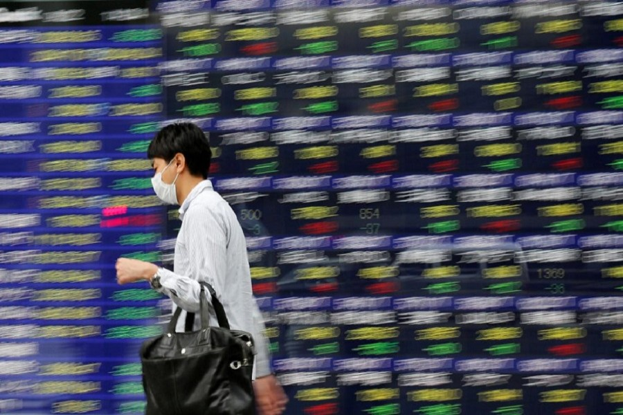 A man walks past an electronic stock quotation board outside a brokerage in Tokyo, Japan, September 22, 2017. Reuters