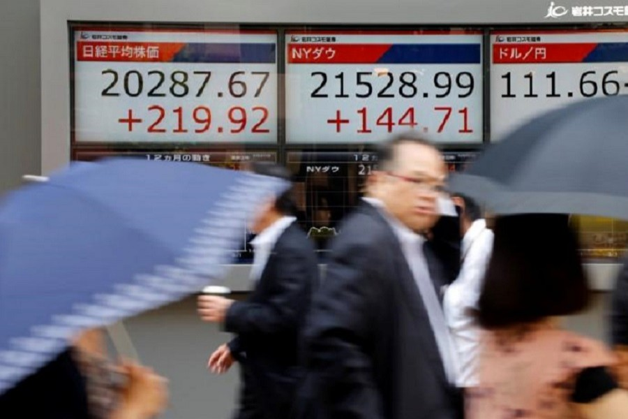 People walk past an electronic board showing Japan's Nikkei average (L), the Dow Jones average (C), and the exchange rates between the Japanese yen and the US dollar outside a brokerage in Tokyo, Japan June 20, 2017. Reuters