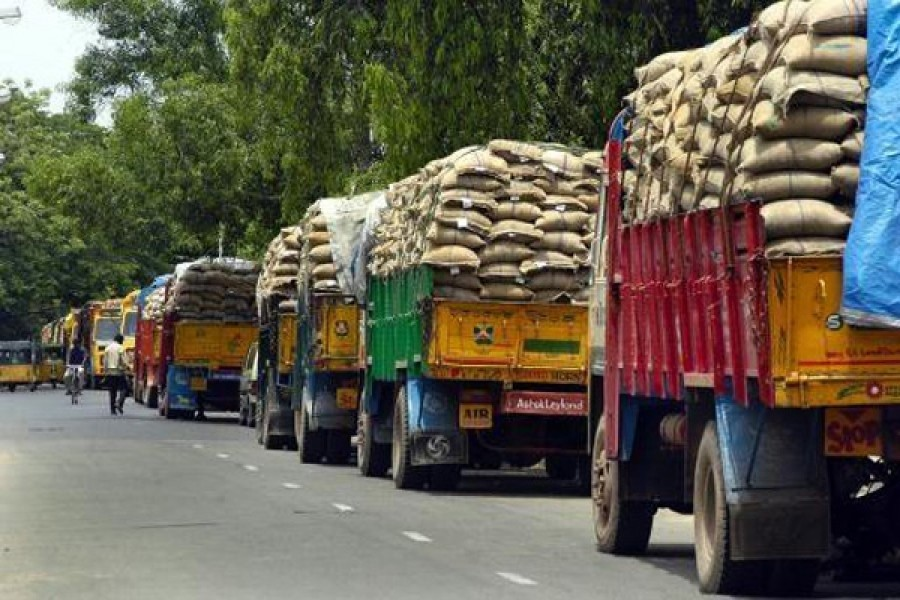File photo shows trucks standing laden with rice, the prices of which have recently soared causing the government to import it from a few countries, including Myanmar and Cambodia.