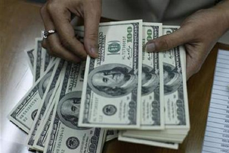 An employee is seen counting US dollar notes at a money changer in this photo: Reuters