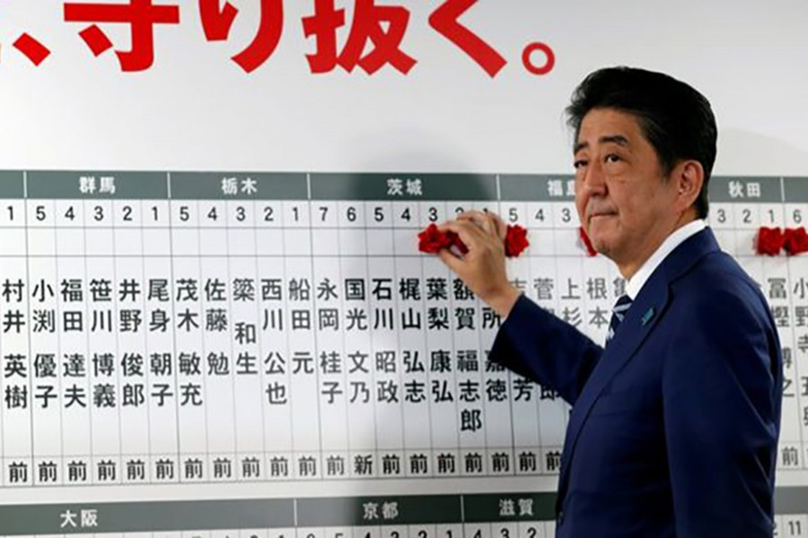 Japan's Prime Minister Shinzo Abe, leader of the Liberal Democratic Party (LDP), puts a rosette next to his name after the lower house election on Sunday. - Reuters