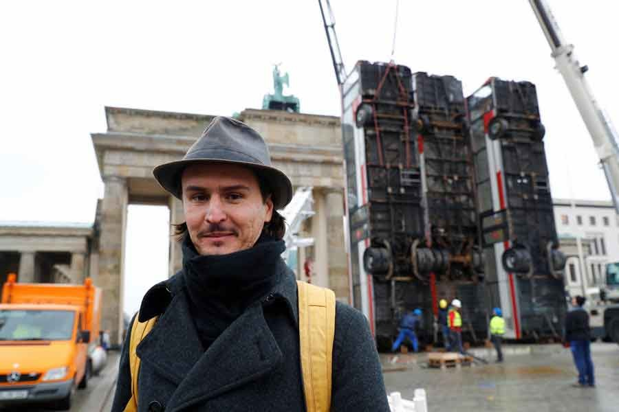 """BERLIN: German-Syrian artist Manaf Halbouni poses in front of his installation """"Monument"""" in front of the Brandenburg Gate in Berlin on Friday.  — Reuters"""