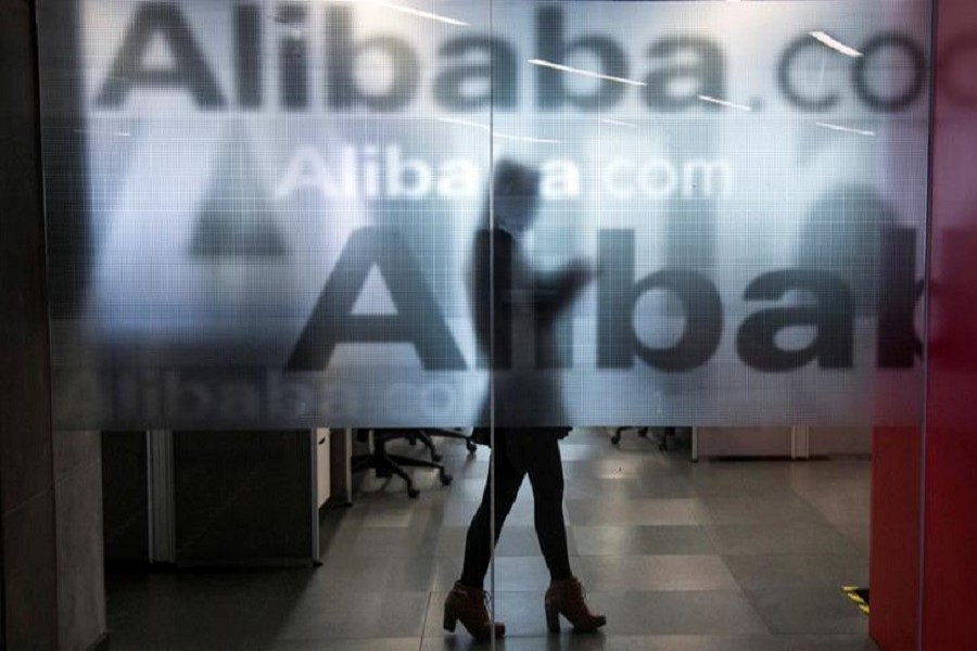 An employee is seen behind a glass wall with the logo of Alibaba at the company's headquarters on the outskirts of Hangzhou, Zhejiang province, April 23, 2014. Reuters/File Photo