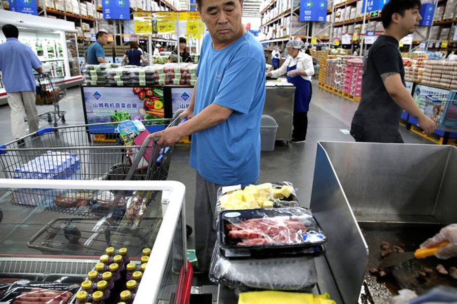 A customer looks at the beef steaks for sale at a Sam's Club store of Wal-Mart in Beijing, China. - Reuters file photo