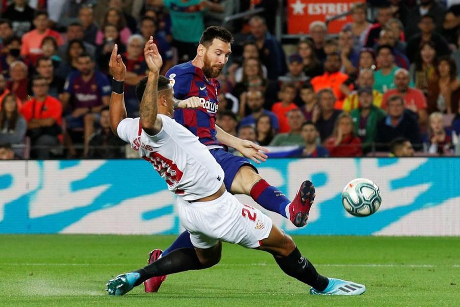Barcelona's Lionel Messi with Sevilla's Diego Carlos — Reuters photo