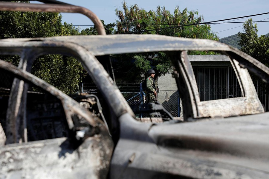 A soldier is seen near the burnt wreckage of a police patrol car after an ambush by suspected cartel on police officers in El Aguaje, in Michoacan state, Mexico on October 14, 2019 — Reuters photo