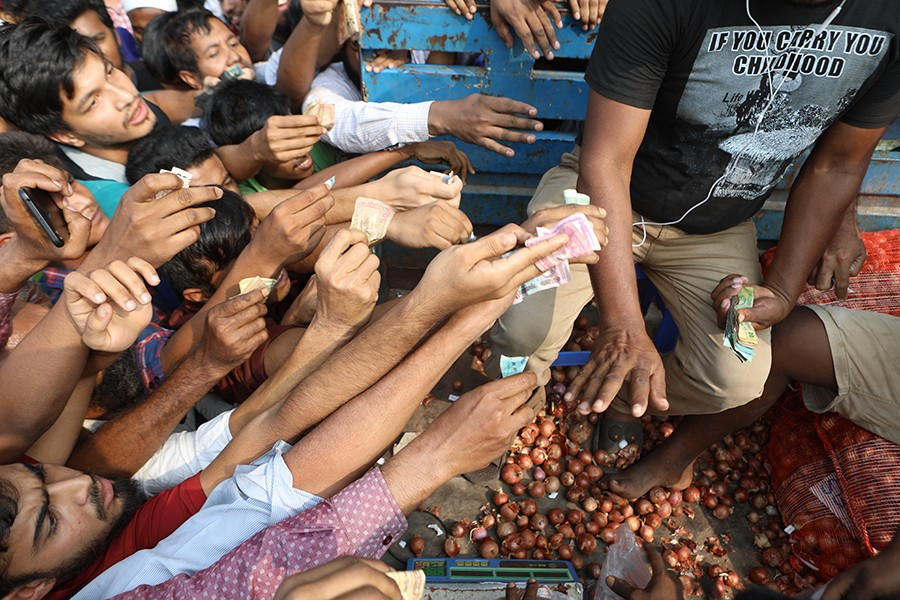 Consumers' frantic efforts to purchase onion at Tk 45 per kg from a TCB-operated truck at Khamarbari in the capital on Sunday amid the soaring prices of the essential — FE Photo by Shafiqul Alam