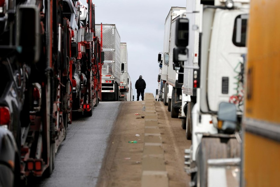 A man stands between trucks waiting in a long queue at border customs control to cross into the US at the Otay border crossing in Tijuana, Mexico, April 3, 2019. Reuters/Files
