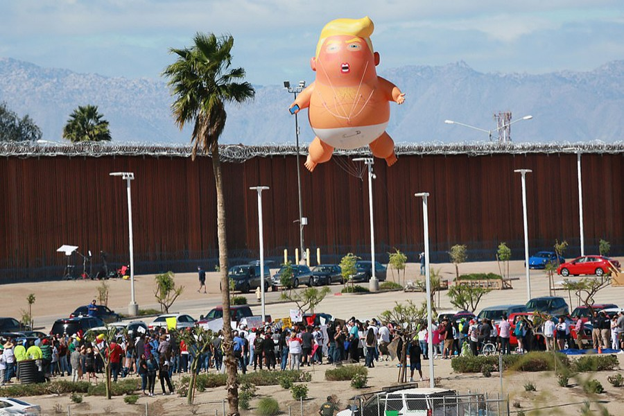 A 'Baby Trump' balloon flies over the US-Mexico border fence — Reuters/Files
