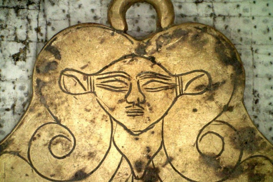 A gold pendant depicted the head of the Egyptian goddess Hathor - a protector of the dead - Photo Courtesy: EPA