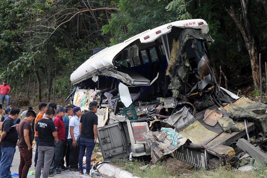 People are pictured on the scene of a collision between a passenger bus and a trailer truck early on Saturday in Gualan, near Guatemala's Atlantic coast, Guatemala on December 21, 2019 — Reuters photo