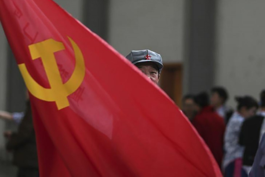 A participant waves a Chinese Communist Party flag as he waits backstage before his performance at a line dancing competition in Kunming, Yunnan province on January 31, 2015 — Reuters/Files