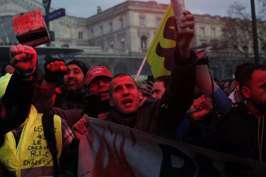 French union members and workers demonstrating in Paris on Thursday after 22 days on a strike against pension reform plans. -AP Photo