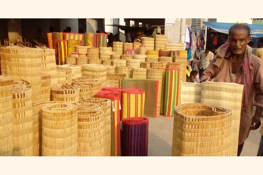 A mele mat seller waiting for buyers at his shop at a market in Satkhira district— UNB Photo