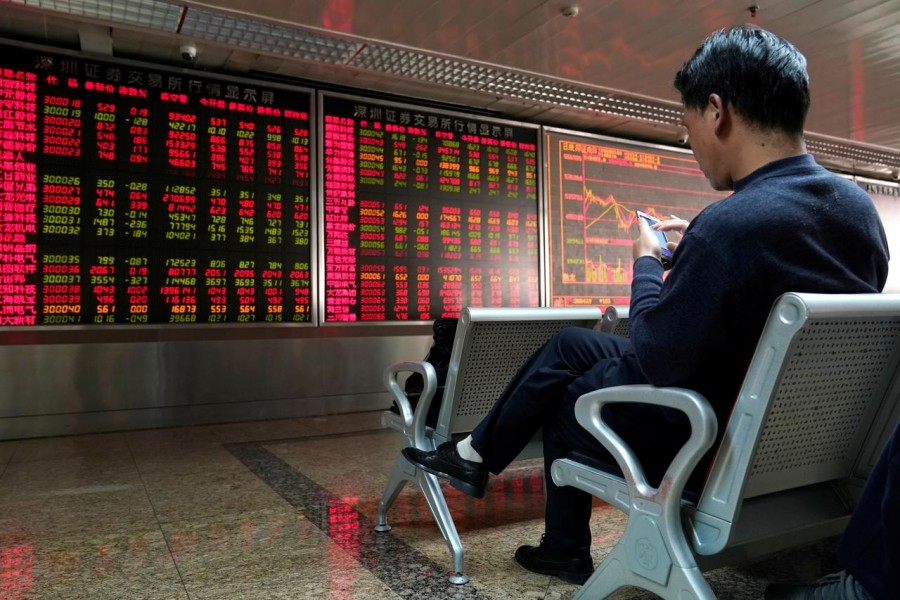 An investor sits next to a stock quotation board at a brokerage office in Beijing, China, January 03, 2020. Reuters