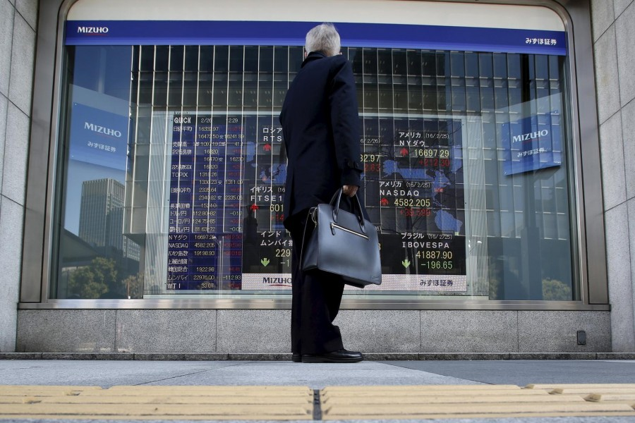 A pedestrian stands to look at an electronic board showing the stock market indices of various countries outside a brokerage in Tokyo, Japan, February 26, 2016. Reuters/Files