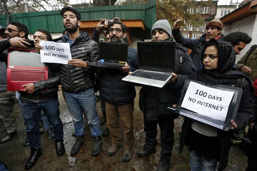 Kashmiri journalists display laptops and placards during a protest demanding restoration of internet service, in Srinagar on November 12, 2019 — REUTERS/Files