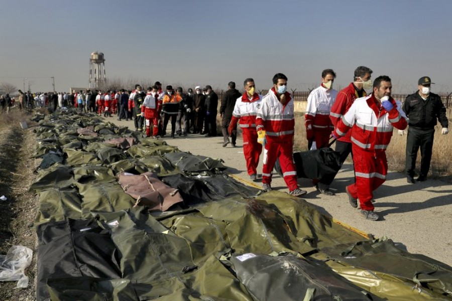 Rescue workers carry the body of a victim of a Ukrainian plane crash in Shahedshahr, southwest of the capital Tehran, Iran, Wednesday, January 8, 2020 -- AP Photo