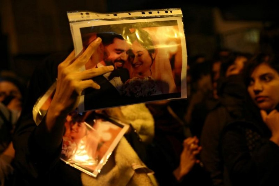 A woman holds a picture of newlyweds, victims of the crash of the Boeing 737-800 plane, flight PS 752, as people gather to show their sympathy in Tehran, Iran, January 11, 2020. Nazanin Tabatabaee/WANA (West Asia News Agency) via Reuters/File Photo