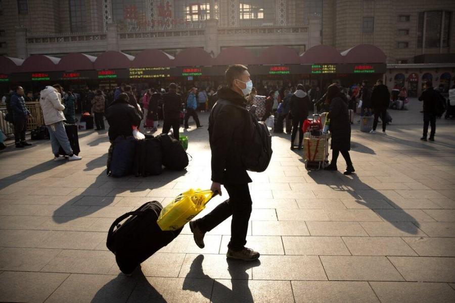 A traveler wears a facemask as he walks in front of the Beijing Railway Station in Beijing, Jan. 17, 2020. (AP Photo)
