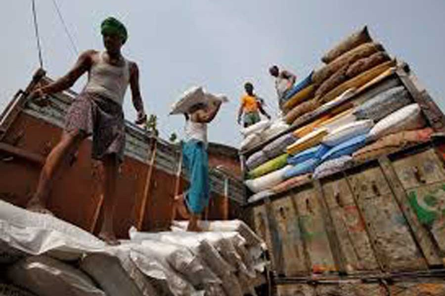 A labourer carries a sack filled with sugar to load it onto a supply truck at a wholesale market in Kolkata, India— Reuters