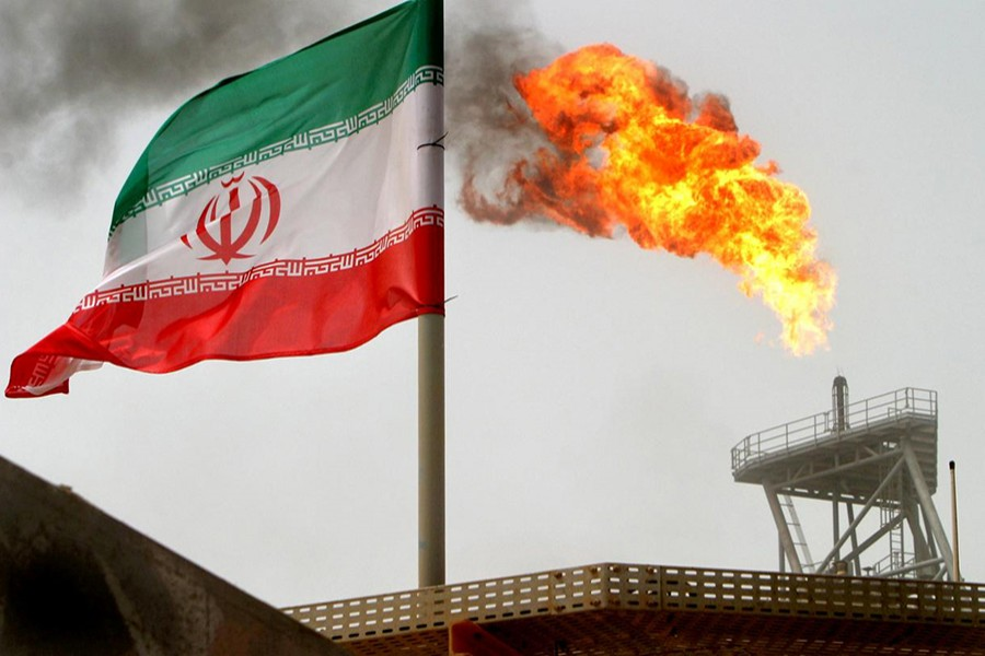 A gas flare on an oil production platform in the Soroush oil fields is seen alongside an Iranian flag in the Persian Gulf, Iran on July 25, 2005 — Reuters/Files