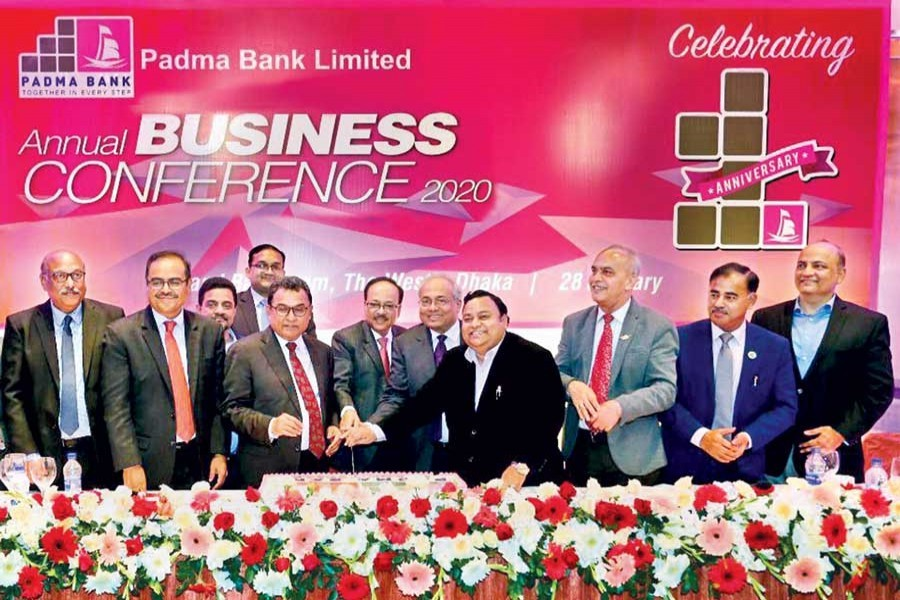 Finance Minister AHM Mustafa Kamal along with directors including Padma Bank Ltd chairman Chowdhury Nafeez Sarafat cutting a cake to mark 1st anniversary of Padma Bank Ltd and also the Annual Business Conference 2020 on Tuesday