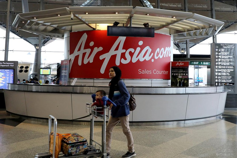 A woman walks past an AirAsia counter at Kuala Lumpur International Airport in Sepang, Malaysia on July 22, 2019 — Reuters/Files
