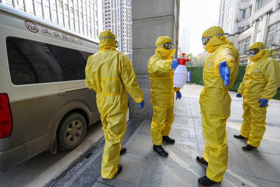 FILE PHOTO: Funeral parlour staff members in protective suits help a colleague with disinfection after they transferred a body at a hospital, following the outbreak of a new coronavirus in Wuhan, Hubei province, China January 30, 2020. China Daily via REUTERS/File Photo