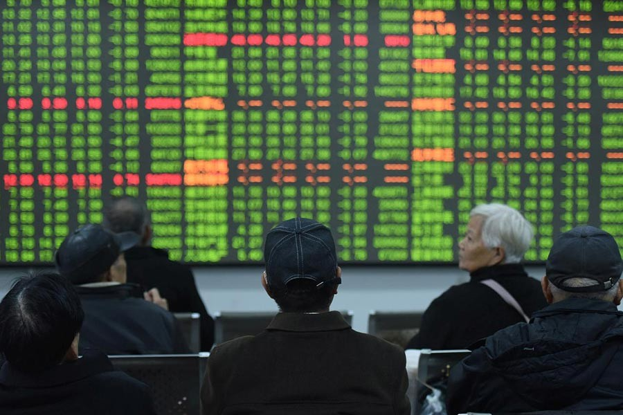 Investors sitting in front of a board showing stock information at a brokerage house on the first day of trade in China since the Lunar New Year, in Hangzhou, Zhejiang province, China this month. -Reuters Photo