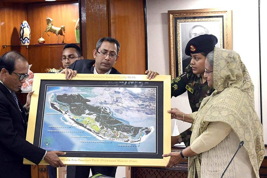 Prime Minister Sheikh Hasina receiving a master plan of a eco-tourism park, to be developed at Cox's Bazar, from concerned officials during a meeting at PMO in Dhaka on Wednesday. -PID Photo