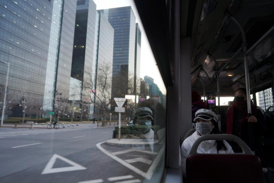 Passengers wearing face mask look on from inside a bus, following an outbreak of the novel coronavirus in the country, in Beijing's central business district, China, February 21, 2020. Reuters