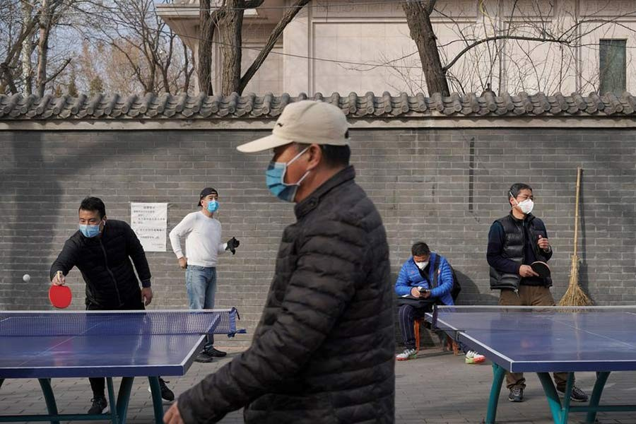 People wearing face masks playing table tennis at a park in Beijing, China, on Friday following an outbreak of the novel coronavirus in the country. -Reuters Photo