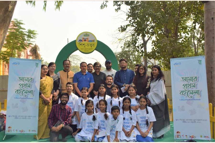 Children taken to Dhaka Ekushe Book Fair for the event 'Amar Prothom Boimela' pose with the organisers