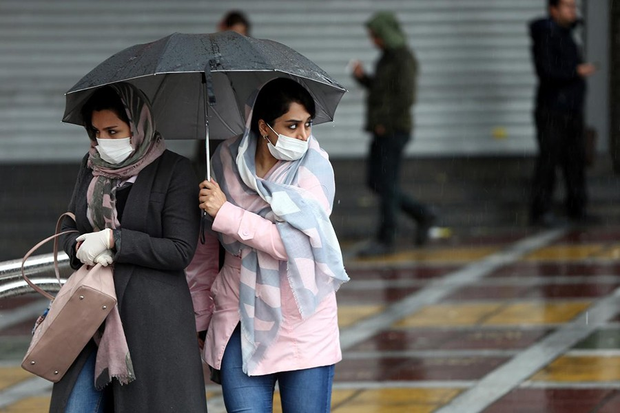 Iranian women wear protective masks to prevent contracting coronavirus, as they walk in the street in Tehran, Iran on February 25, 2020 —  West Asia News Agency via REUTERS