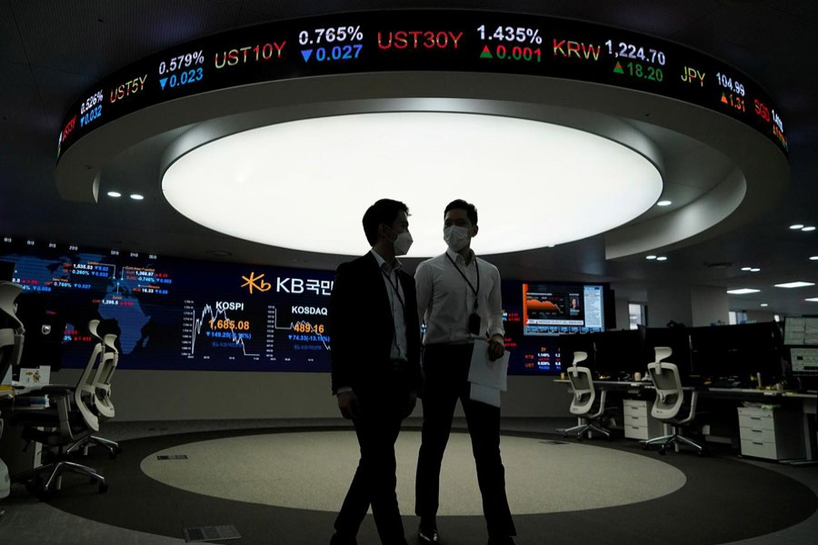 Currency dealers walk past an electronic board showing the Korea Composite Stock Price Index (KOSPI) at a dealing room of a bank in Seoul, South Korea, March 13, 2020 — Reuters