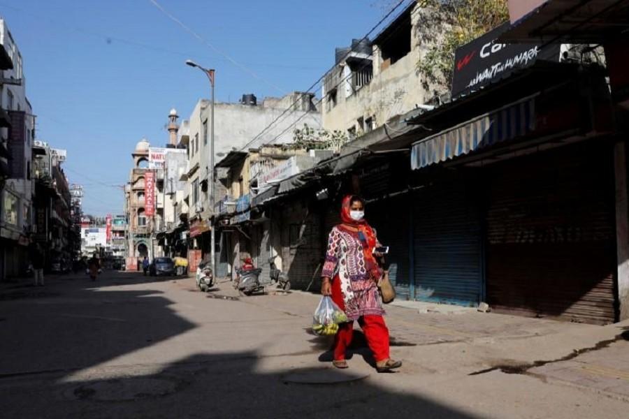 A woman walks along a near-empty street during a lockdown amid a coronavirus disease (COVID-19) outbreak in New Delhi, India, March 25, 2020. — Reuters