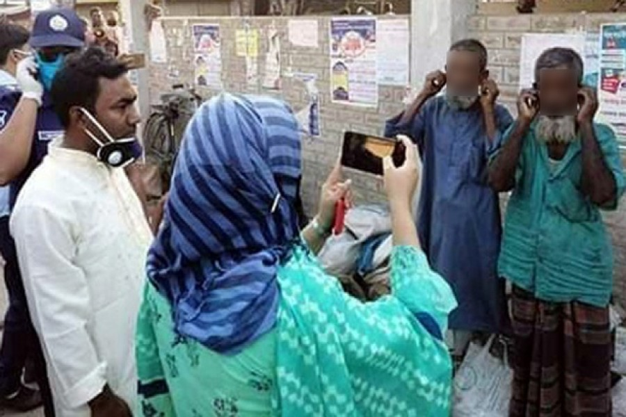 Moniranpur assistant commissioner, or AC, (land) Sayeema recording on her mobile phone two elderly men pulling their ears in a form of punishment handed down by her for their failure to wear masks during the coronavirus outbreak. — Photo Collected