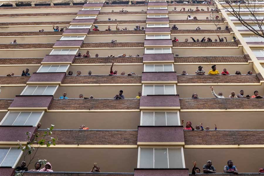 Residents of the densely populated Hillbrow neighborhood of downtown Johannesburg in South Africa, confined in an attempt to prevent the spread coronavirus, standing and waving from their balconies on Friday. –AP Photo