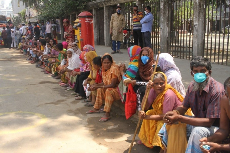 Low-income people waiting to collect relief materials amid a coronavirus shutdown in the country. — UNB Photo