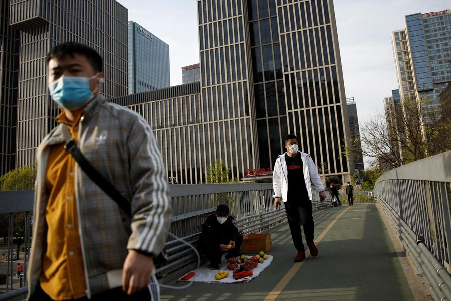 People wearing face masks walk on an overpass in Beijing's central business area, amid an outbreak of the novel coronavirus disease (COVID-19) in the country, China on April 5, 2020  — Reuters photo