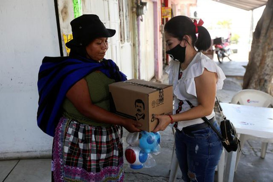 """An employee of the clothing brand """"El Chapo 701"""", owned by Alejandrina Gisselle Guzman, daughter of the convicted drug kingpin Joaquin """"El Chapo"""" Guzman, hands out a box with food, face masks and hand sanitisers to an elderly woman as part of a campaign to help cash-strapped elderly people during the coronavirus disease (COVID-19) outbreak, in Guadalajara, Mexico on April 16, 2020 — Reuters photo"""
