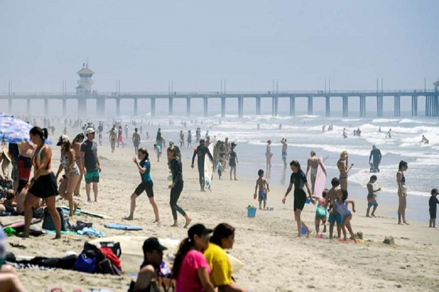 People walk up and down Huntington City Beach during the outbreak of the coronavirus disease (COVID-19), in Huntington Beach, California, US, April 25, 2020. — Reuters
