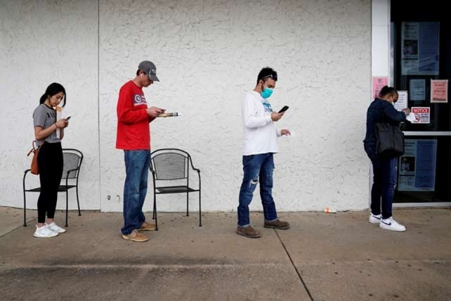 People who lost their jobs wait in line to file for unemployment following an outbreak of the coronavirus disease (COVID-19), at an Arkansas Workforce Centre in Fayetteville, Arkansas, US, April 06, 2020. — Reuters