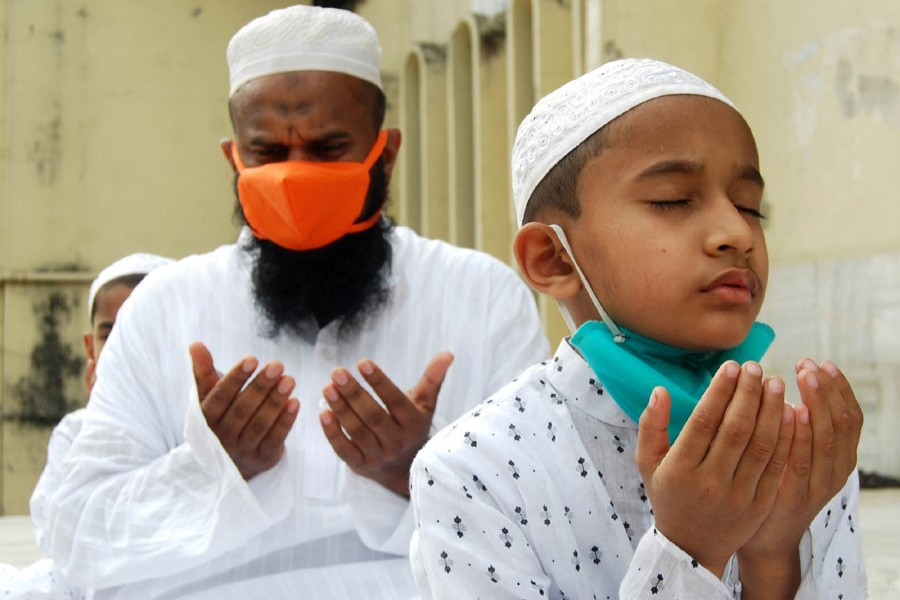 Devotees, wearing masks and maintaining physical distance, offer Munajat after taking part in Eid prayers at Baitul Mukarram National Mosque in the capital on Monday — Focus Bangla photo