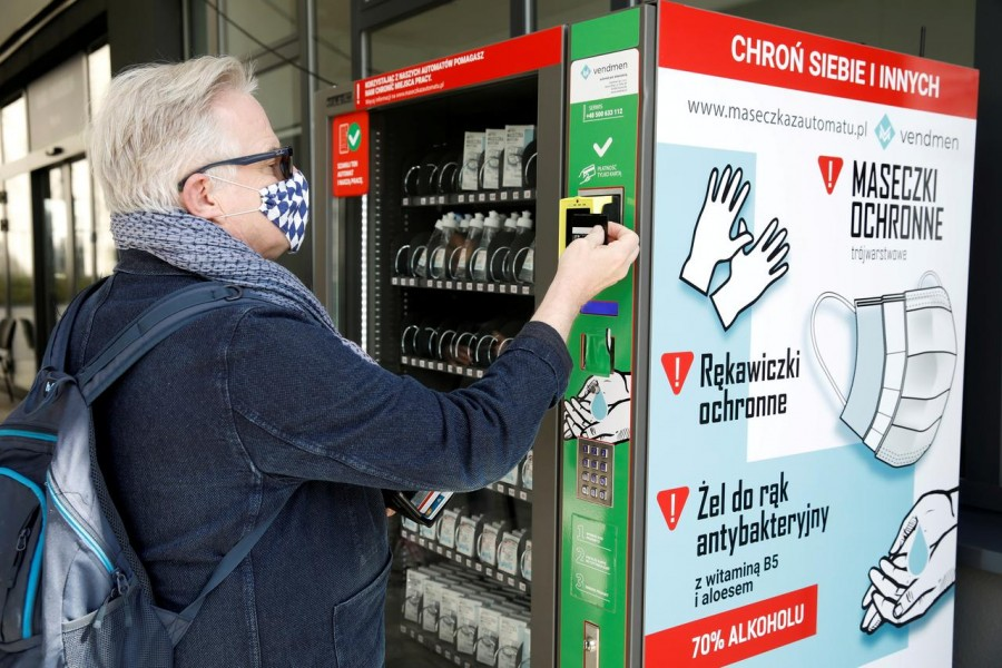 A man uses a vending machine for face masks, gloves, and sanitiser during the coronavirus disease (COVID-19) outbreak, in Warsaw, Poland on April 10, 2020 — Reuters/Files