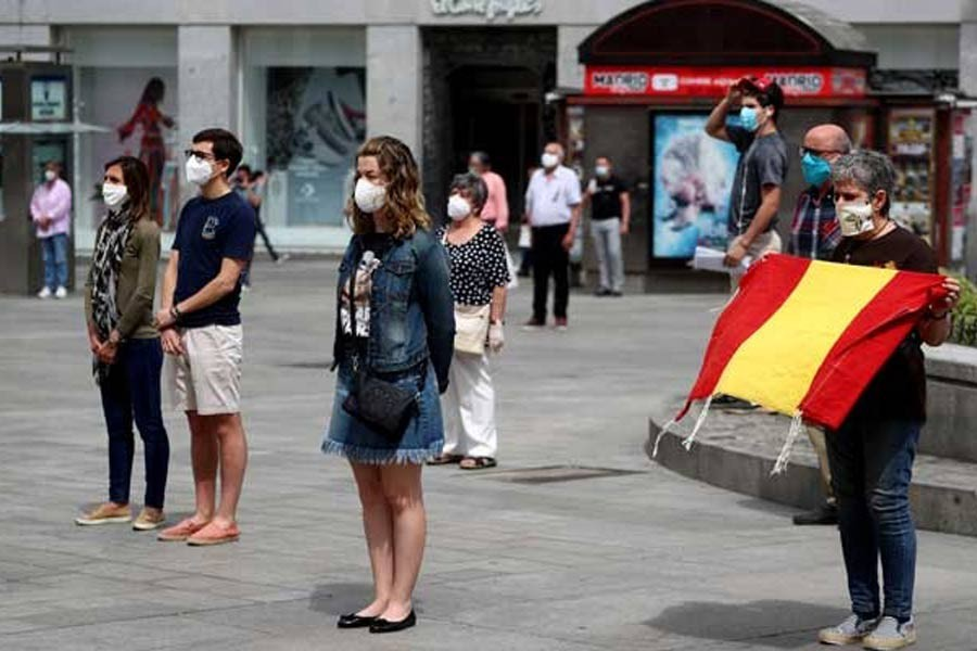 People observing a daily minute of silence to commemorate victims of the coronavirus disease (COVID-19), at Puerta del Sol square in Madrid in Spain recently. –Reuters Photo