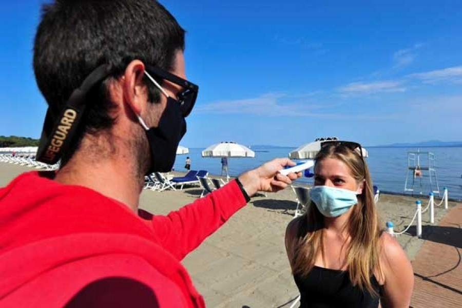 A lifeguard wearing a protective face mask takes the temperature of a woman at a newly reopened beach after months of closure due to an outbreak of the coronavirus disease (COVID-19), at Punta Hidalgo, in Punta Ala, Italy, May 31, 2020. — Reuters